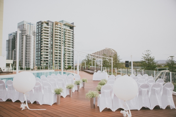 Wedding ceremony on the pool deck with white theme and giant balloons
