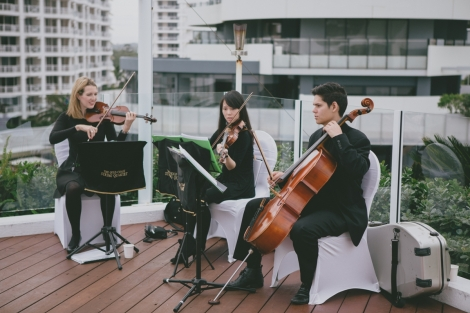 String quartet playing at the wedding ceremony on the pool deck.